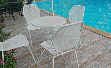 White metal outdoor table and chairs on wood deck near pool