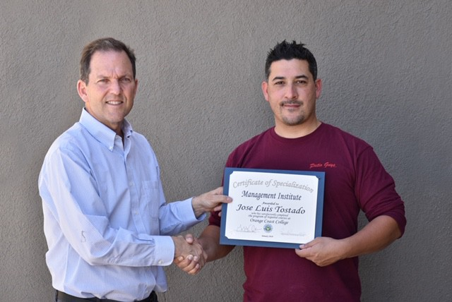 Patio Guys owner shaking hands with employee holding a management institute certificate
