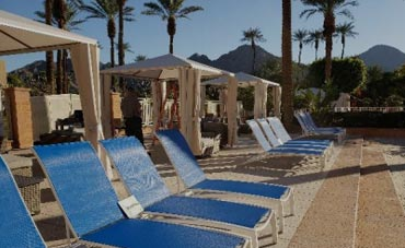 Row of blue sling chaise lounges at hotel