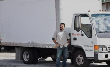 Patio Guys driver standing and smiling in front of Patio Guys truck