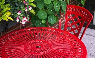 Red metal table and chair by green leaves
