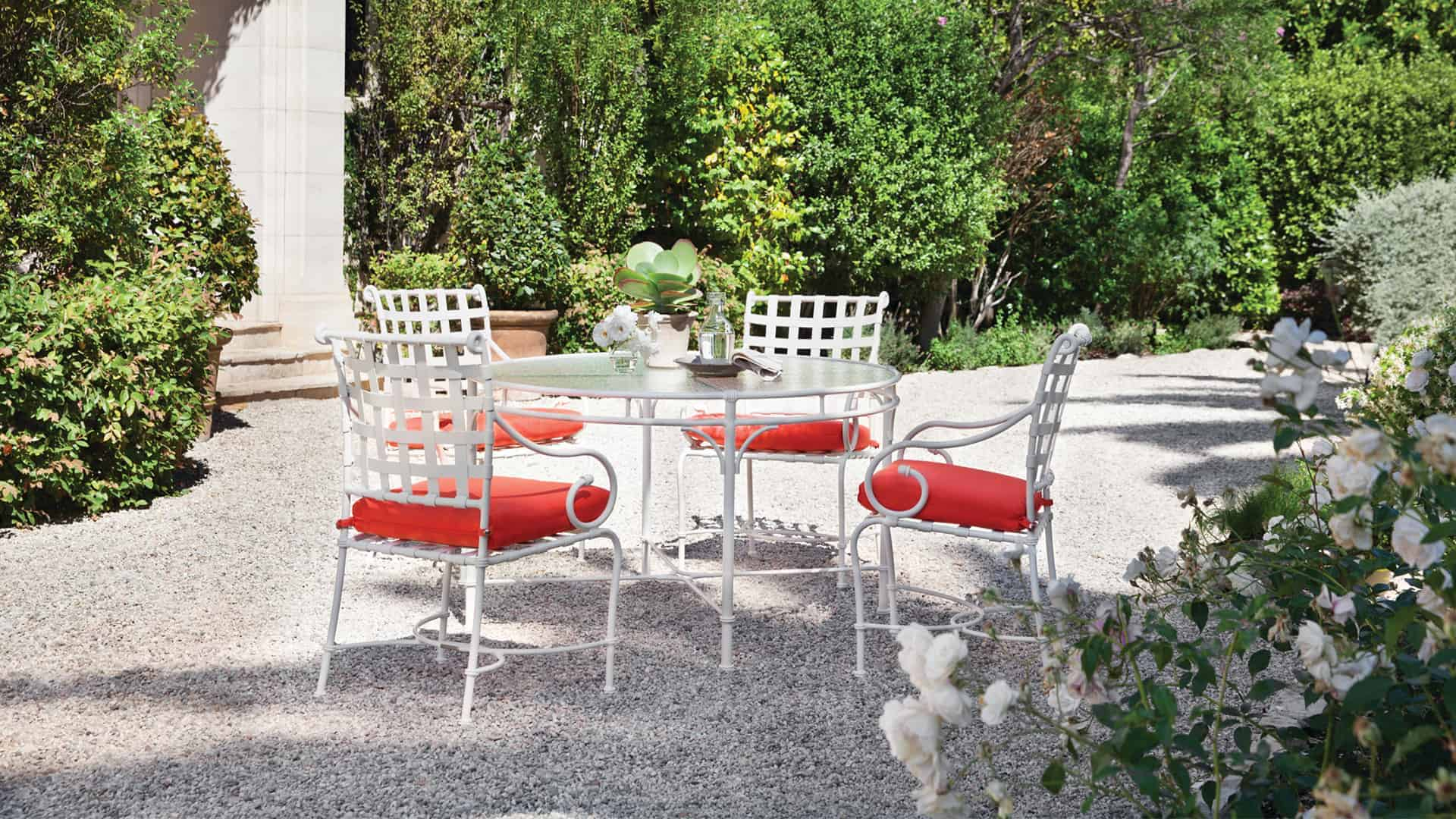 garden dining set with bright salmon cushions in rose garden