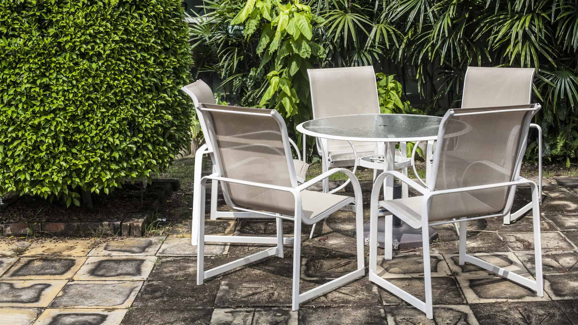 sling chairs and acrylic table in front of green garden hedge