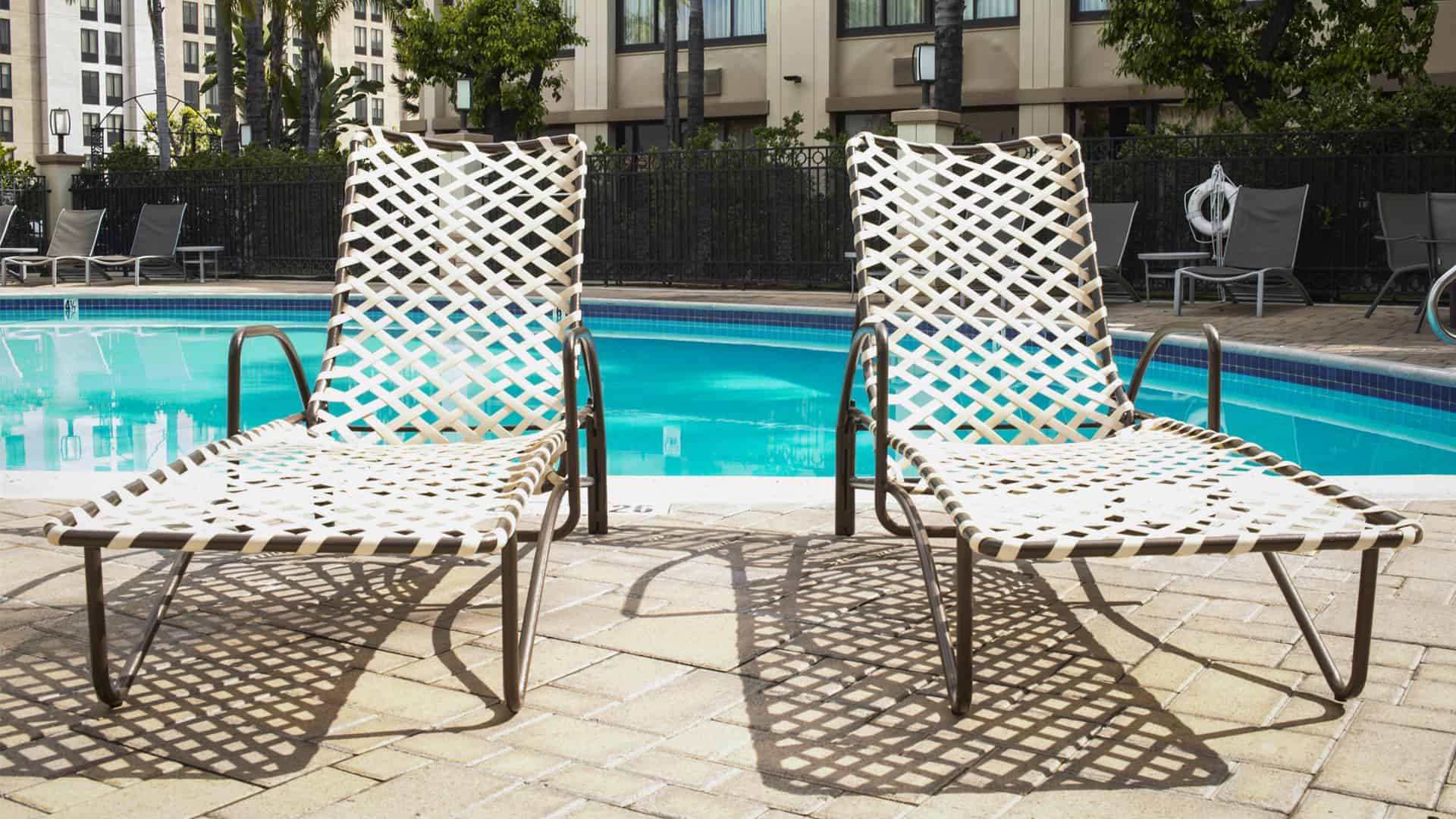 Two chaise lounges with vinyl strap in front of a hotel pool