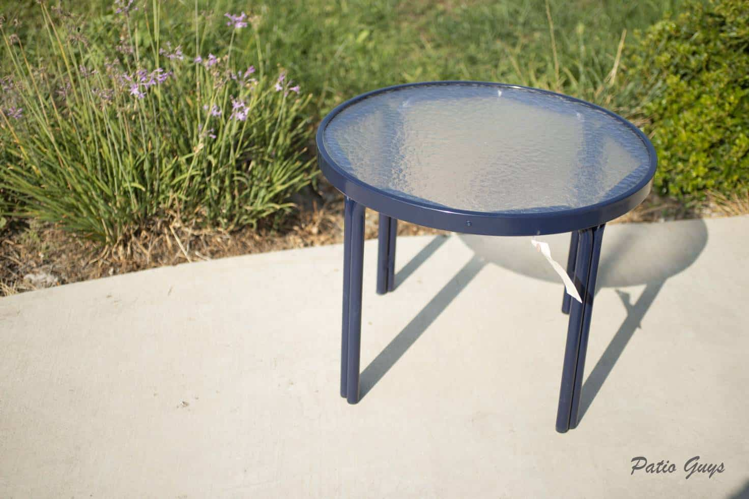 small round navy outdoor side table in front of grass and flowers